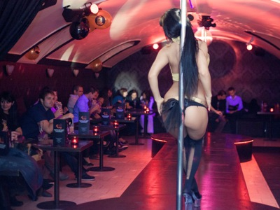Photo of stripper dancing on pole and lots of guys watching in 4Play Lounge Budapest