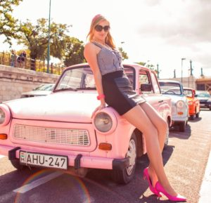 Local blondie Maria leaning on a pink Trabant in Budapest