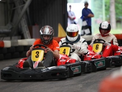 Three go kart racers right behind each other, tight race