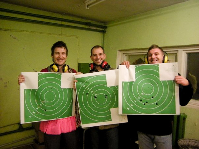Three lads on a Riga stag do with target sheets after shooting