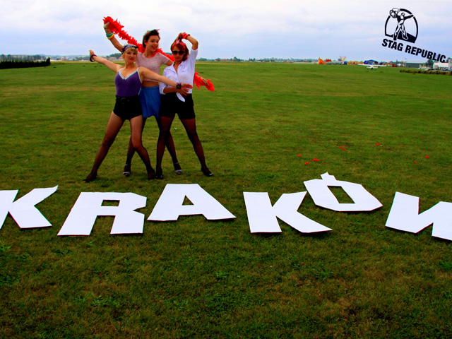Krakow stag guides on grass field with city name sign