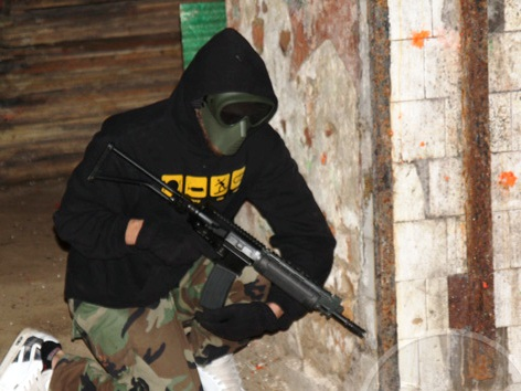 Photo of bloke during airsoft game with mask and gun
