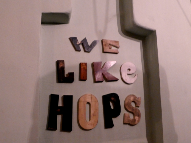 """A sign that says """"We Like Hops"""" on the wall of a Budapest ruin pub"""